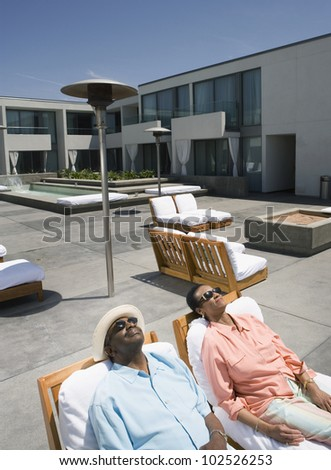 Senior African couple relaxing in deck chairs - stock photo