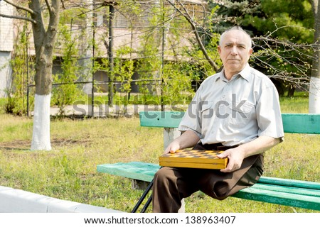 Senior amputee sitting on a park bench with a box of chess pieces on his lap and his crutches alongside him - stock photo