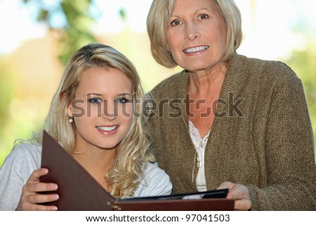 Senior and her granddaughter looking at photos - stock photo