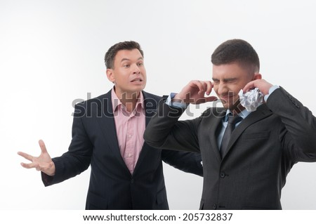 Senior and junior business people, boss angry with young handsome employee holding hands to ears with crumpled paper isolated on white - stock photo