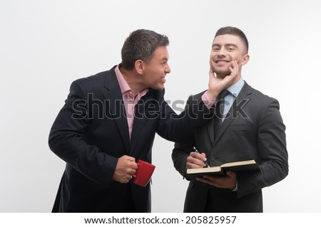 Senior and junior business people communicating, boss with red cup patting face of young employee, isolated on white background - stock photo