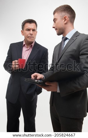 Senior and junior business people discuss something during their meeting holding coffee cup and tablet,  low angle isolated on white background - stock photo