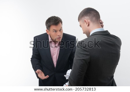 Senior and junior business people in elegant suits. Boss angry with young handsome employee standing from behind, holding crumpled paper isolated on white - stock photo