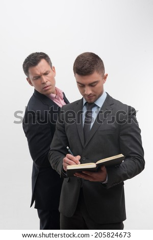 Senior and junior business people in suits, young handsome employee writing in notebook in front, senior colleague peeping from his back, isolated on white - stock photo