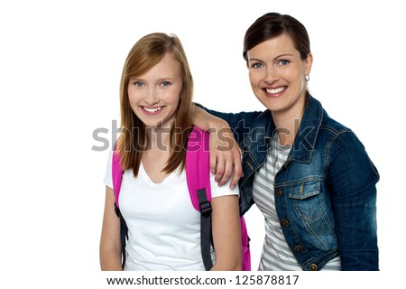Senior and junior college colleagues. Lady dressed in fashion wear whereas girl in casuals carrying backpack. - stock photo