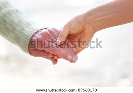 Senior and young holding hands over shiny white background - stock photo