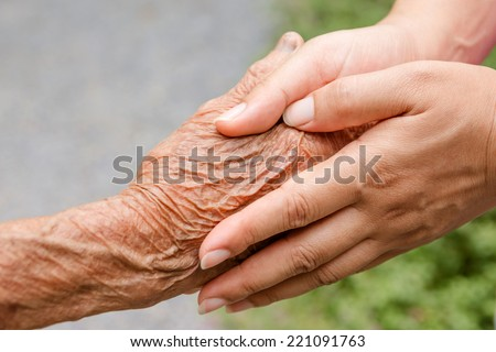 Senior and young holding hands with retro effect - stock photo