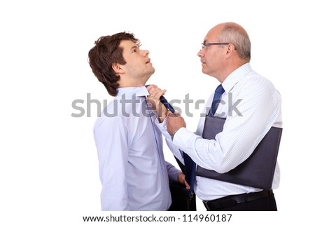 Senior angry businessman with briefcase tearing young businessman at his tie, isolated on white background - stock photo