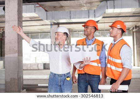 Senior architect is expressing his ideas concerning building. He is pointing his arm sideways and smiling. The man is holding a blueprint. The builders are looking aside with interest and joy - stock photo