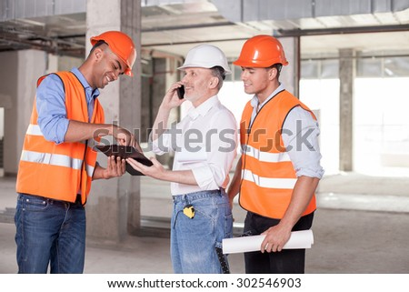 Senior architect is talking on the phone with his boss. Project was approved. The builders are smiling happily. The foreman is pointing his finger at the folder of documents. Copy space in right side - stock photo