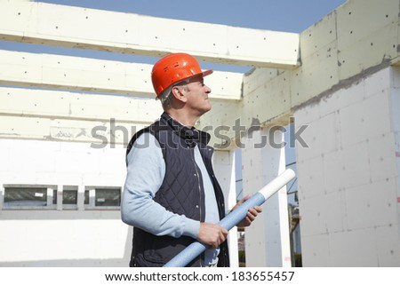Senior architect standing in front of building, while using his mobile. Small business. - stock photo