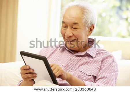 Senior Asian man using tablet - stock photo