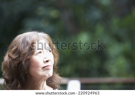 Senior Asian woman looking to side - stock photo