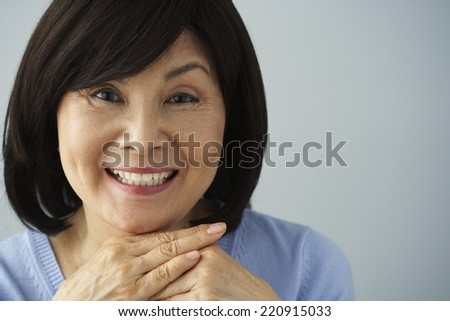 Senior Asian woman resting chin on hands - stock photo