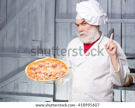 Senior bearded chef with pizza in white uniform with serious face and hat on wooden background - stock photo