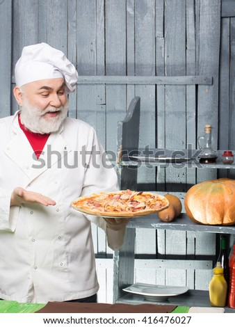 Senior bearded chef with pizza in white uniform with smiling face and hat on wooden background - stock photo