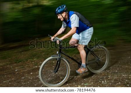 Senior beim radfahren im Wald - stock photo