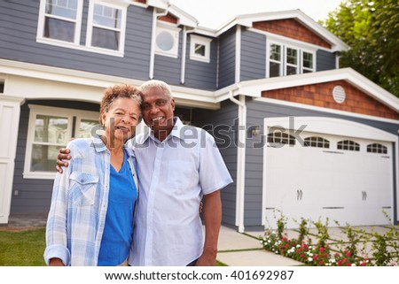 Senior black couple standing outside a large suburban house - stock photo