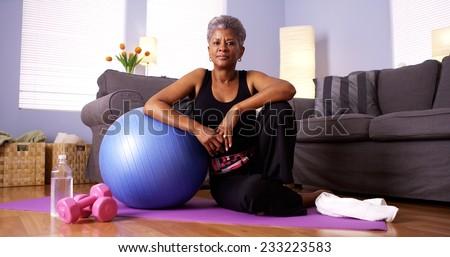 Senior Black woman sitting on floor with exercise equipment - stock photo