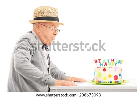 Senior blowing candles on his birthday cake isolated on white background - stock photo