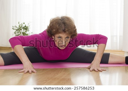Senior brown haired woman  laying on the parquet floor and  exercising yoga at home. - stock photo
