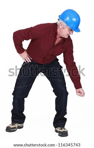 Senior builder struggling to bend over - stock photo