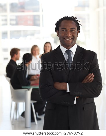 Senior business leader standing and smiling in front of his team - stock photo