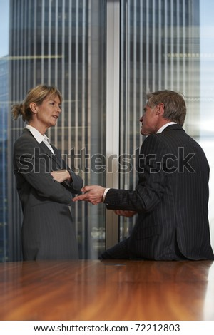 Senior business man and woman in a boardroom having a conversation - stock photo