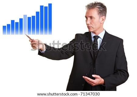 Senior business man pointing to financial statistics - stock photo