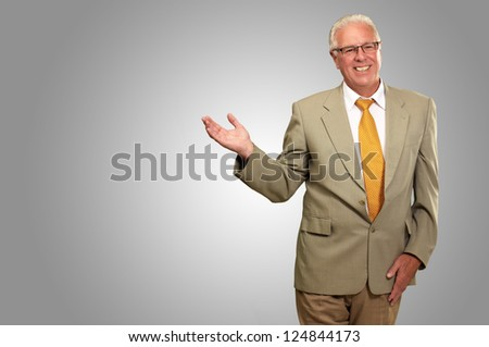 Senior Business Man Presenting Isolated On gray Background - stock photo