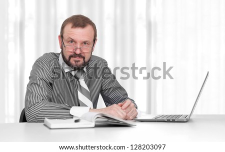 senior business man sitting by his desk in the office - stock photo