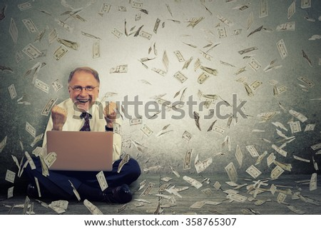 Senior business man using a laptop building online business making money dollar bills cash falling down. Money rain. IT entrepreneur online job success economy concept - stock photo