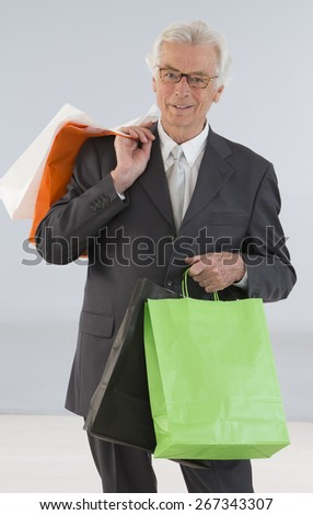 senior business man with shopping bags - stock photo