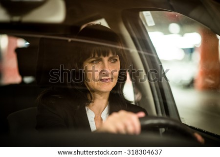 Senior business woman driving car at night - view through front window - stock photo