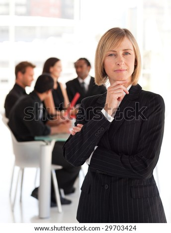 Senior business woman in foreground with team in Background - stock photo