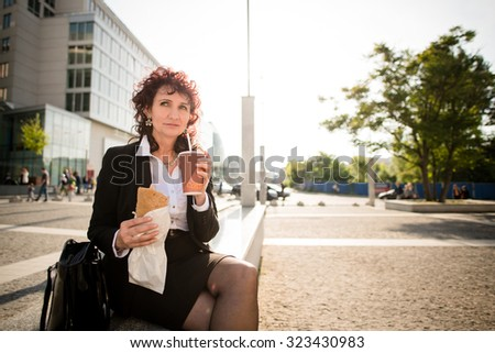 Senior business woman on fast food lunch - drinking take-away coffee and eating sandwich in street - stock photo