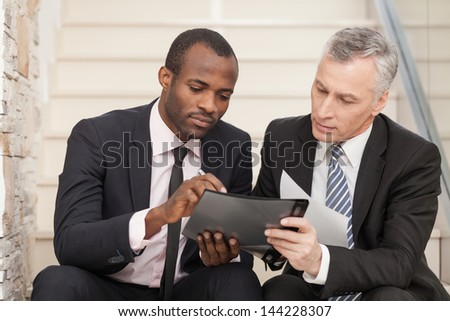 Senior businessman and mid adult businessman working together. They are sitting on staircase and reading a papers - stock photo