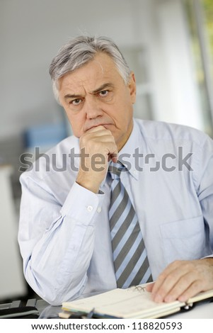 Senior businessman being serious in front of client - stock photo