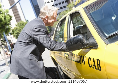 Senior businessman discussing his fare with a taxi driver - stock photo