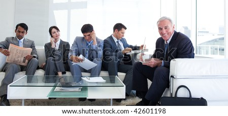 Senior businessman drinking a coffee in a waiting room - stock photo
