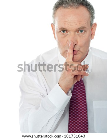 Senior businessman gesturing silence - stock photo