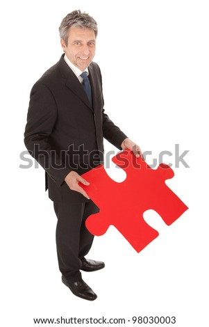 Senior businessman holding a jigsaw puzzle. Isolated in white - stock photo