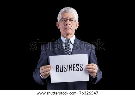 Senior businessman holding a paper with the Business word (isolated on black) - stock photo