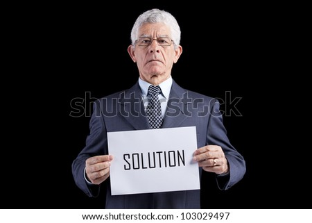 Senior businessman holding a paper with the solution word (isolated on black) - stock photo