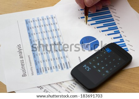 senior businessman holding a pen, analyzing blue charts with calculator - stock photo