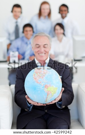 Senior businessman holding a terrestrial globe with his colleagues in the background - stock photo