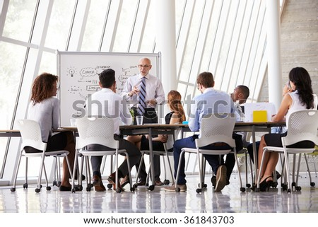 Senior Businessman Leading Meeting At Boardroom Table - stock photo