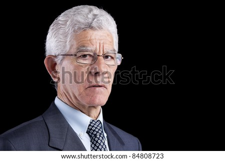 Senior businessman looking to you (isolated on black) - stock photo