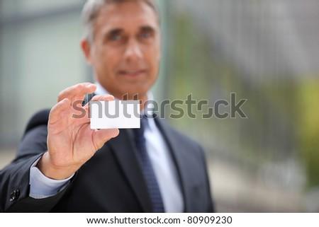 Senior businessman offering business card - stock photo