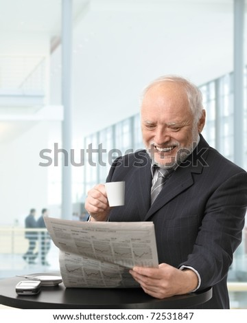 Senior businessman on coffee break in office lobby, reading papers, holding coffee cup, smiling.? - stock photo